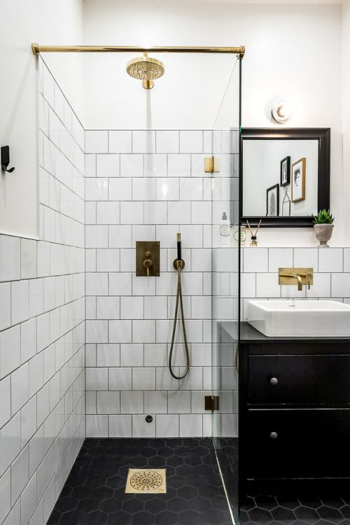 a small monochromatic bathroom with white and black hex tiles, a black vanity and a black frame mirror plus touches of gold