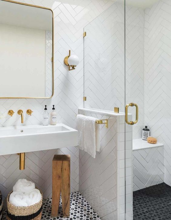 a small monochromatic bathroom with white herringbone tiles, printed black ones on the floor and touches of gold