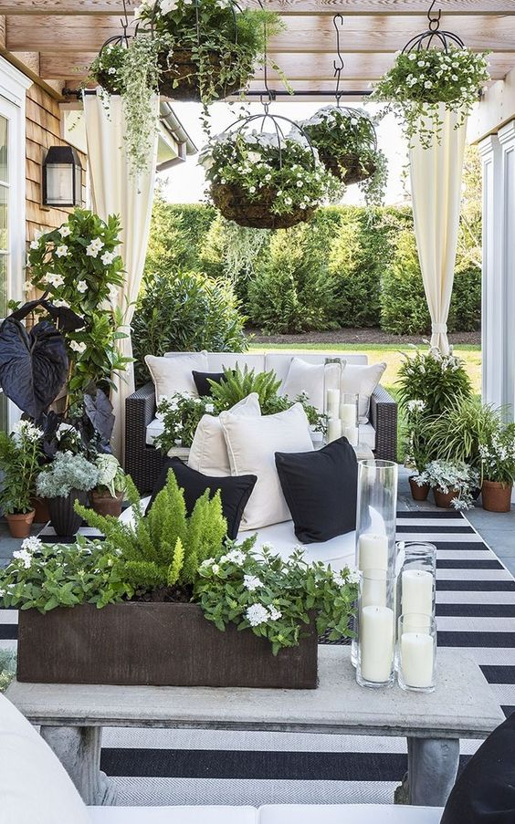 a small monochromatic patio with a striped rug, a black sofa, a bench, candles and lots of greenery and white blooms