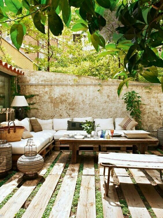 a small patio with a corner sofa, a wooden table, wicker candle lanterns, a wooden plank floor and some greenery