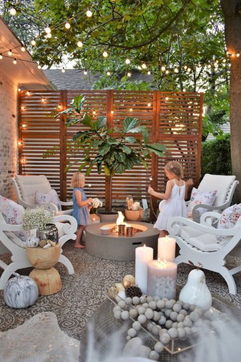 a small patio with a tile floor, a concrete fire pit, vintage chairs, a potted tree, lights, candles and blooms