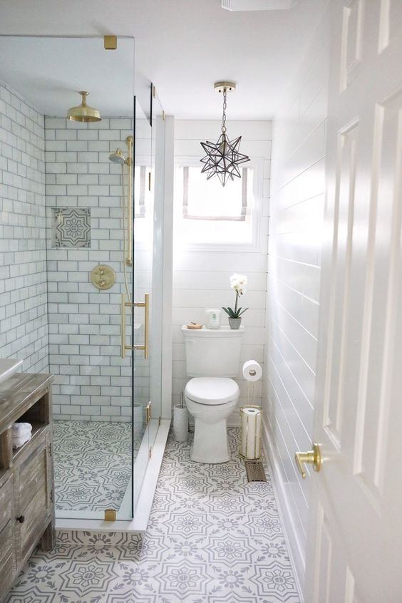 a small peaceful bathroom with white subway tiles, pritned floor, touches of gold and a star-shaped pendant lamp