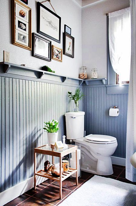 a small powder room with powder blue beadboard, a window, a gallery wall and some dark tiles on the floor