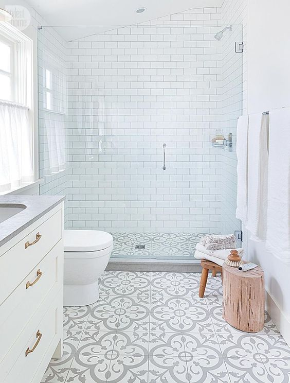 a small serene bathrooms with white subway tiles, patterned ones on the floor, wooden furniture and a window with a curtain