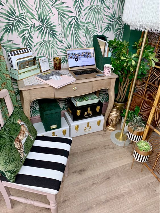 a small tropical home office with an accent wall, a rattan screen, gold planters, various boxes, tropical pillows and touches of brass