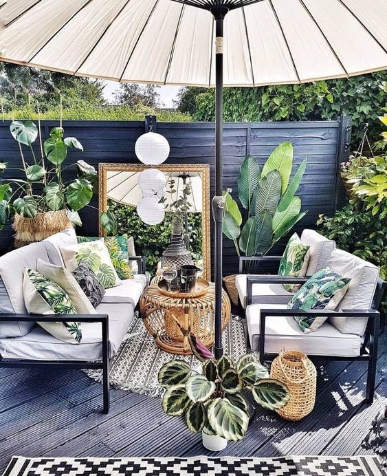 a small tropical patio done in black and grey, with white furniture, a large umbrella, potted plants and tropical pillows