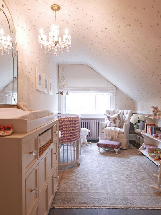 a small vintage-inspired attic nursery with a crystal chandelier, a large dresser, some furniture for the kid and adults
