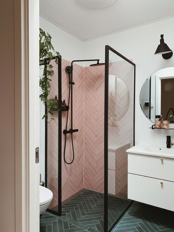 a small yet catchy bathroom with pink herringbone tiles and grene ones, a white vanity and black fixtures here and there