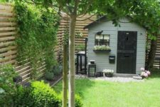 a small yet elegant backyard garden with a grene lawn, some shrubs and a tree plus a wall with climbing greenery