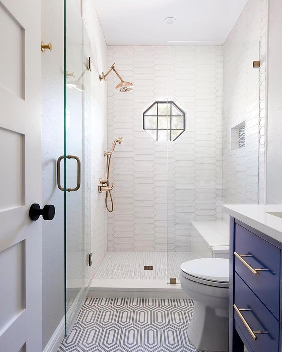 a small yet stylish bathroom with catchy long tiles in the shower and patterned ones ont he floor, with a bold blue vanity, brass touches and a geometric window