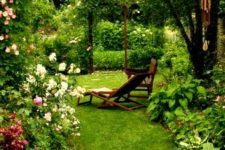 a small yet very lush garden with a manicured lawn, greenery, pink flowers and an arch with climbing greenery and blooms