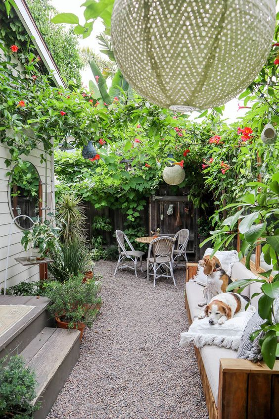a small yet very lush patio with a sofa, pendant lamps, lots of greeneyr and pink blooms and a small dining set