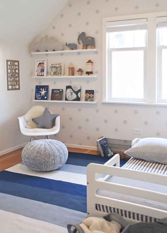 a starry nursery with a star printed wall, blue textiles, an open shelf and lots of toys and books