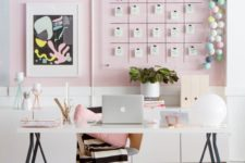 a stylish contemporary home office with light pink walls, a gallery wall with a calendar, a lightweight desk and pink accessories