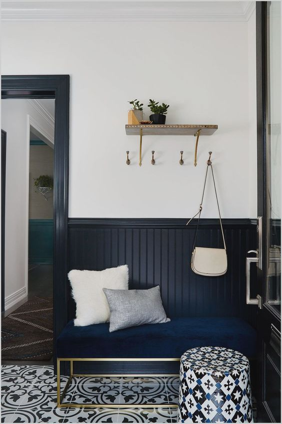 a stylish entryway with midnight blue beadboard, a navy bench, printed tiles on the floor and a bright printed ottoman