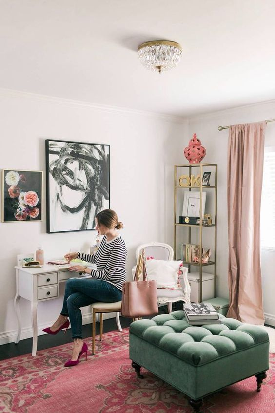 a stylish home office with blush curtains, a pink printed rug, some accessories and a grene ottoman for an eclectic look and feel