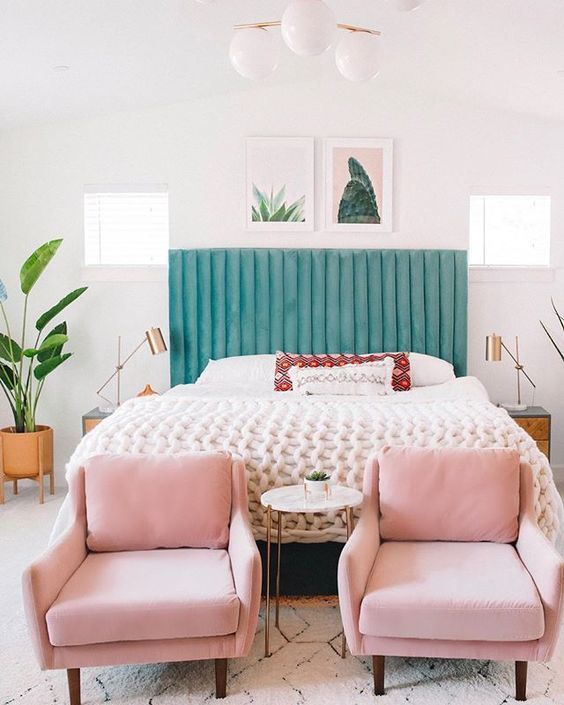 a stylish modern bedroom in neutrals spruced up with a green bed, pink chairs and a cool gallery wall that ties up these colors