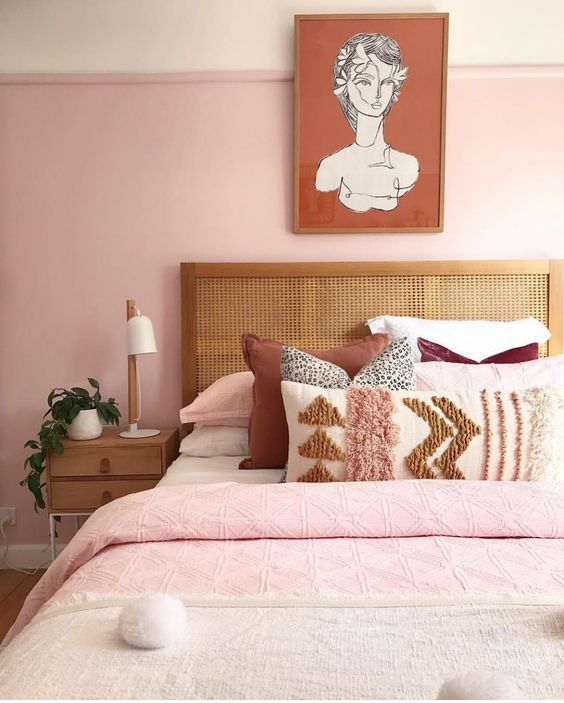 a stylish modern bedroom with light pink walls, pink, neutral and burgundy bedding, wooden furniture and a statement artwork