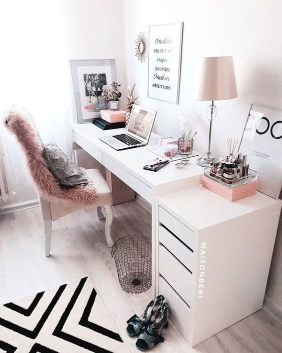 a stylish monochromatic home office with a faux fur cover, pink accessories and a pink lamp plus a graphic rug