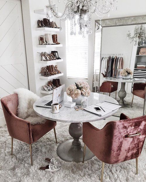 a super glam cloffice with an oversized mirror, a crystal chandelier, dusty pink velvet chairs, a vintage table and open shelves for shoes