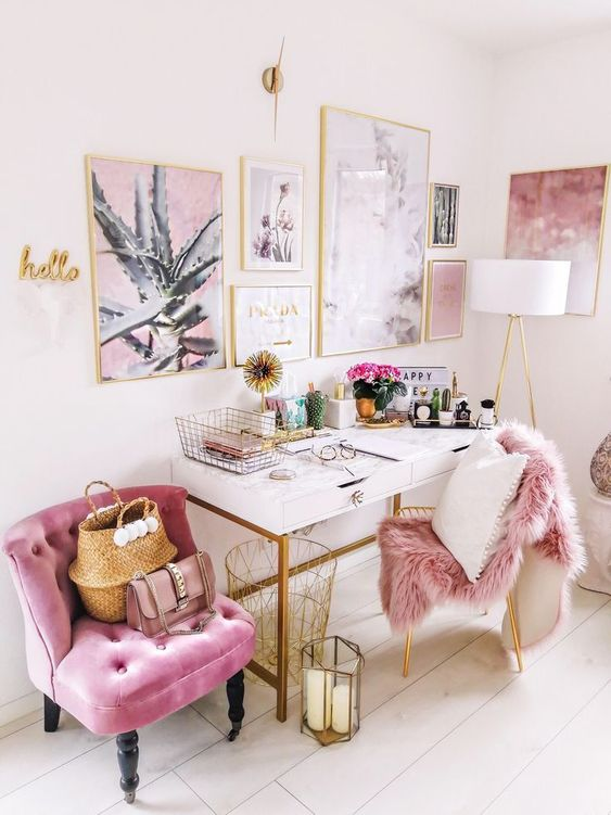 a super glam home office with a gorgeous gallery wall in gold frames, a pink chair and a faux fur cover is very welcoming