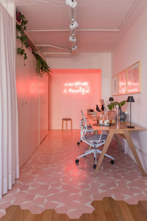 a super modern home office with a pink wall and neon lights, a pink gallery wall, a pink and white tile floor and sleek storage units