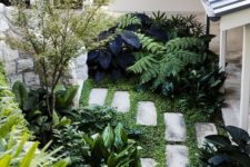 a tiny garden nook with greenery, lots of various shrubs and a small tree plus stone paves