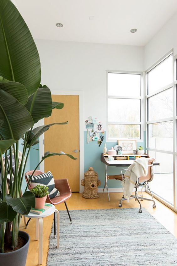 a tropical home office done with sand and water colors, with a woven trash can, tropical plants and leather chairs