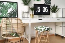 a tropical home office in neutrals, with a tropical gallery wall, potted plants, a rattan chair and stool and touches of gold