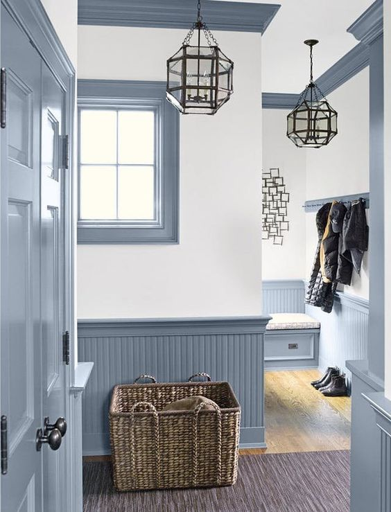 a vintage farmhouse entryway with light blue beadboard, pendant lamps, a basket box and much natural light