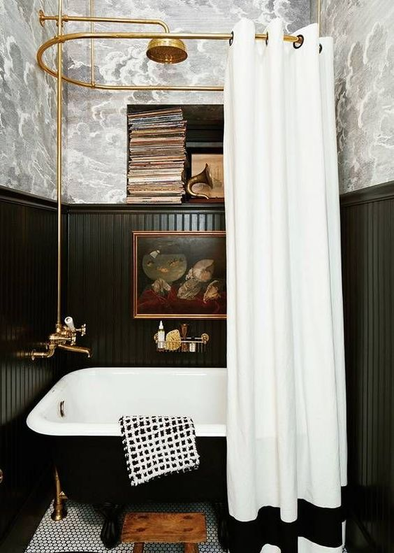 a vintage-inspired bathroom done with wallpaper and black beadboard, a black tub, vintage books and artworks