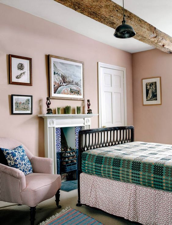 a vintage-inspired farmhouse bedroom with wooden beams, blush walls, a fireplace, green and pink printed textiles here and there