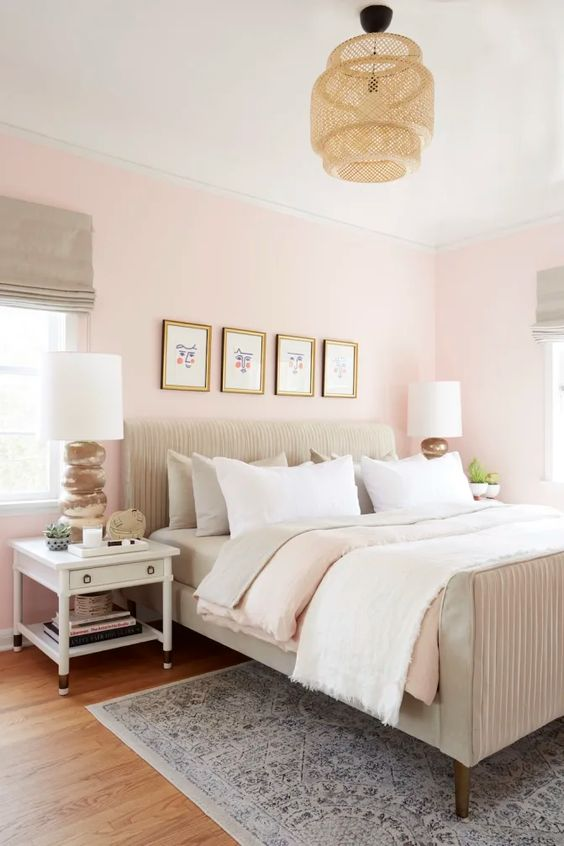 a welcoming modern bedroom with light pink walls, a neutral bed, a wicker lamp and white furniture and a gallery wall