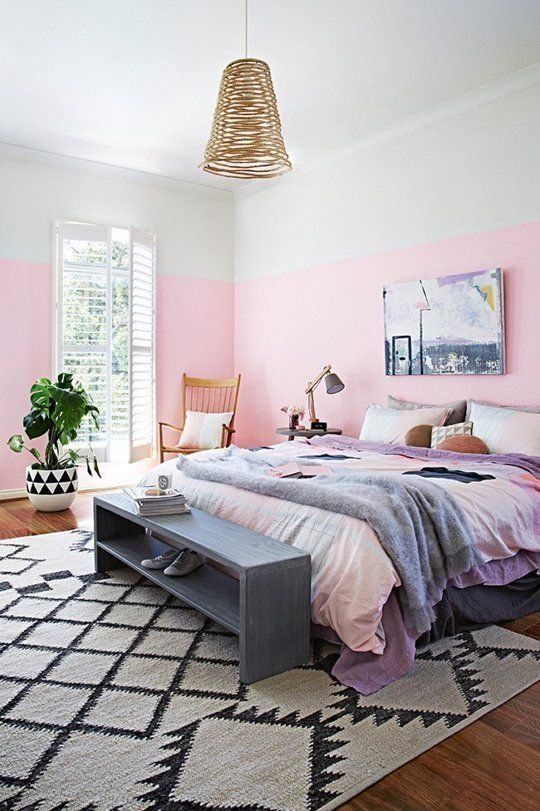 a whimsy modern bedroom with bright color block walls, a wicker lamp, colorful bedding, wooden furniture and a statement plant