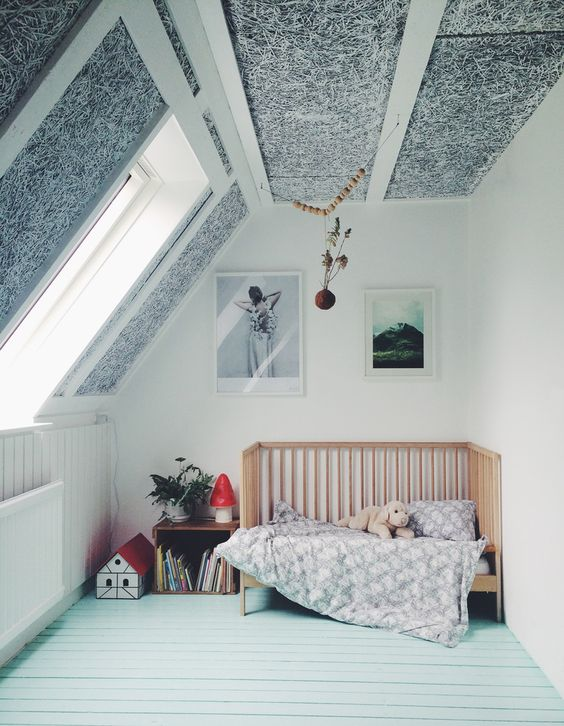 an attic nursery with a mint floor, a black and white paneled ceiling, a crib and some toys and storage units