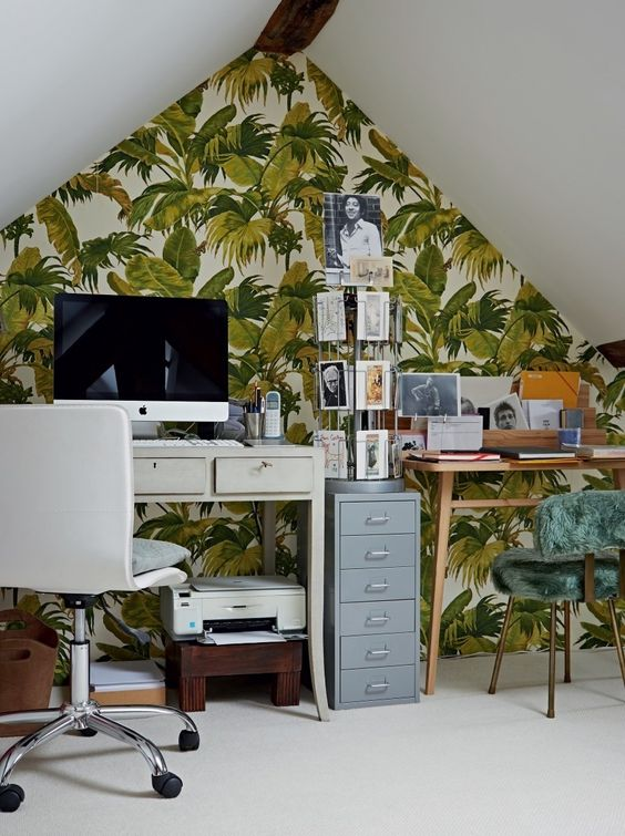 an attic tropical home office with an accent wall, two desks, a green fur chair, a stand with cards and a white chair