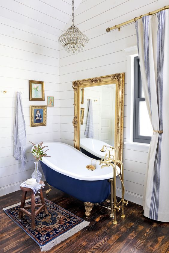 an eclectic bathroom clad with white beadboard, with a navy tub, a statement mirror, a crystal chandelier and a gallery wall