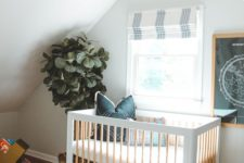 an eclectic nursery with black and white decor, with a statement potted plant, layered rugs, a leather ottoman
