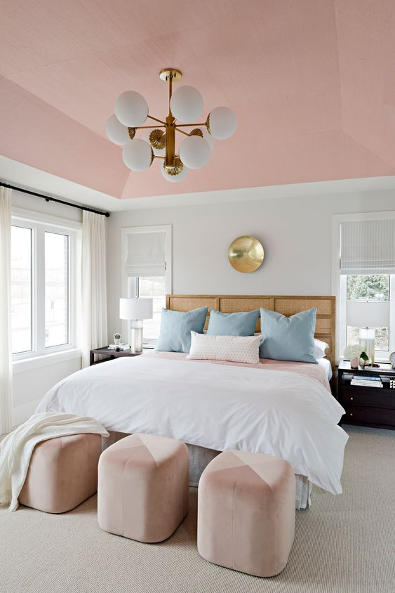 an elegant modern bedroom with a pink ceiling and color block ottomans, blue pillows and touches of gold