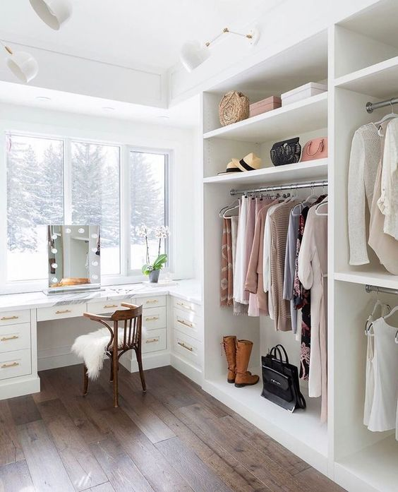 an ethereal cloffice with a large white open closet and a built-in desk or vanity table plus a gorgeous view