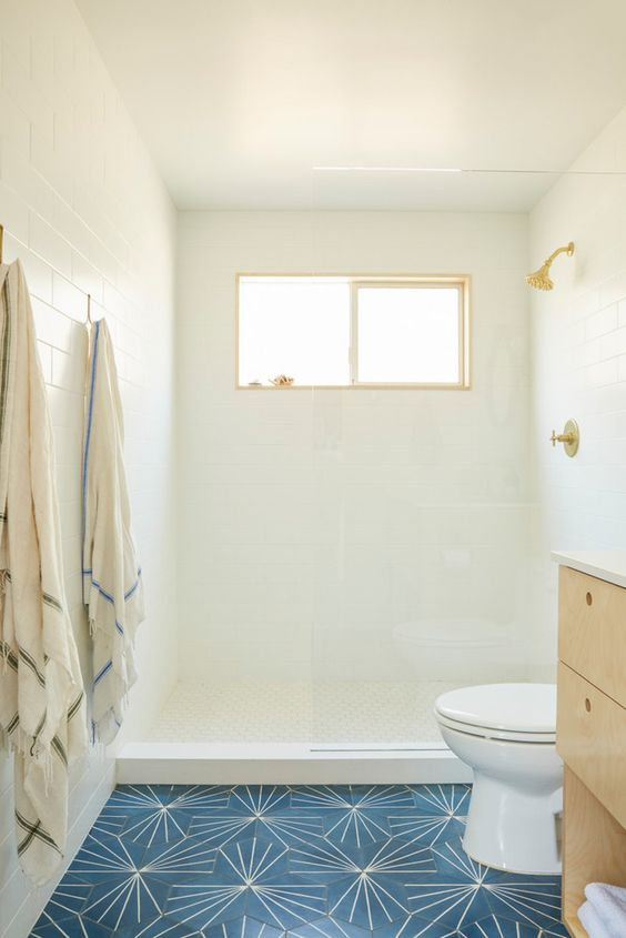 white tiles on the walls and ceilings, navy tiles on the floor, a light-colored wooden vanity and a small window is inviting