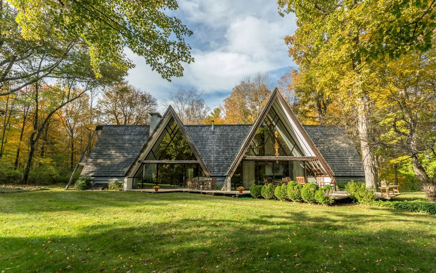 This beautiful mid century modern home features severla A frame sections and is surrounded with woods