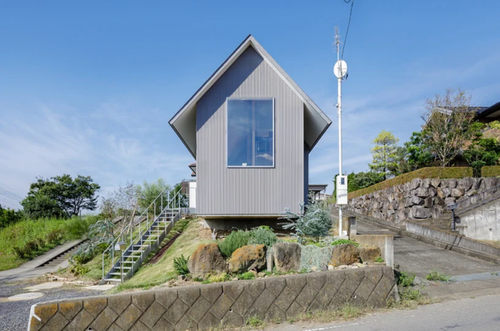 This minimalist Japanese home is built into a hill and features foundations at three different heights