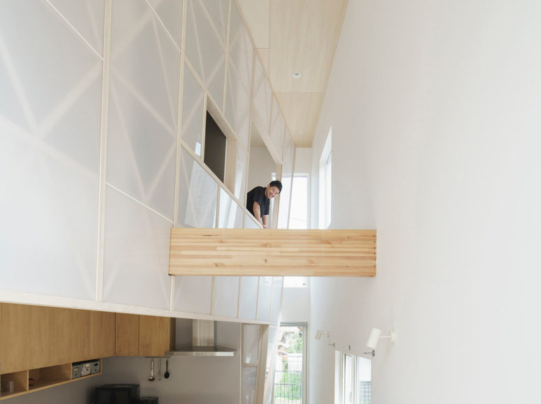 The interior shows off a cool transparent acrylic curtain that divides spaces without depriving them of natural light