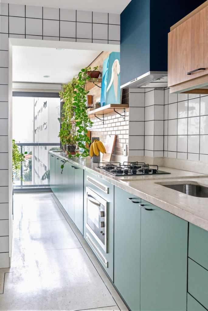 The kitchen is long and narrow, done with green cabinets, white terrazzo countertops, blush and white tile backsplashes
