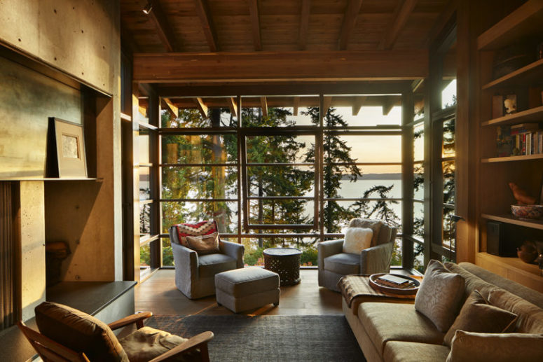The living room shows off a glazed wall with forest and coastal views, a built-in fireplace and modern furniture