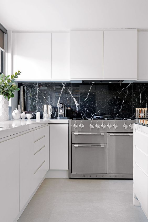a black marble kitchen backsplash is a very luxurious touch to these ultra-minimalist white cabinets
