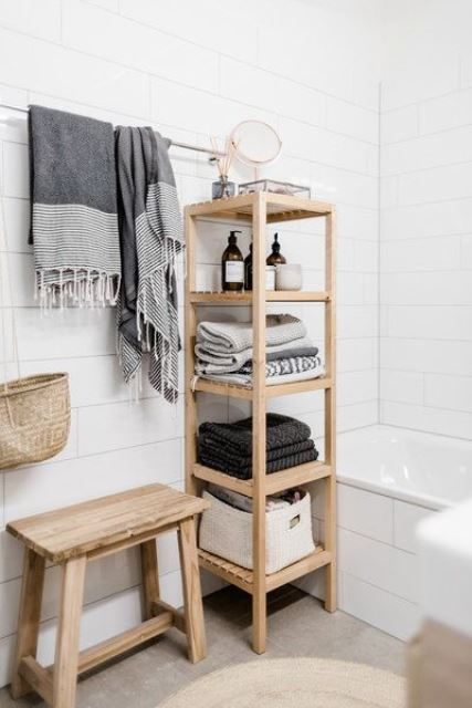 a minimalist wooden shelf with towels and various necessary bathroom stuff and railing for towels over it
