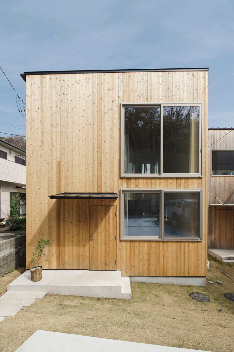 The house is clad with light-colored wood on the outside and several windows bring much light in