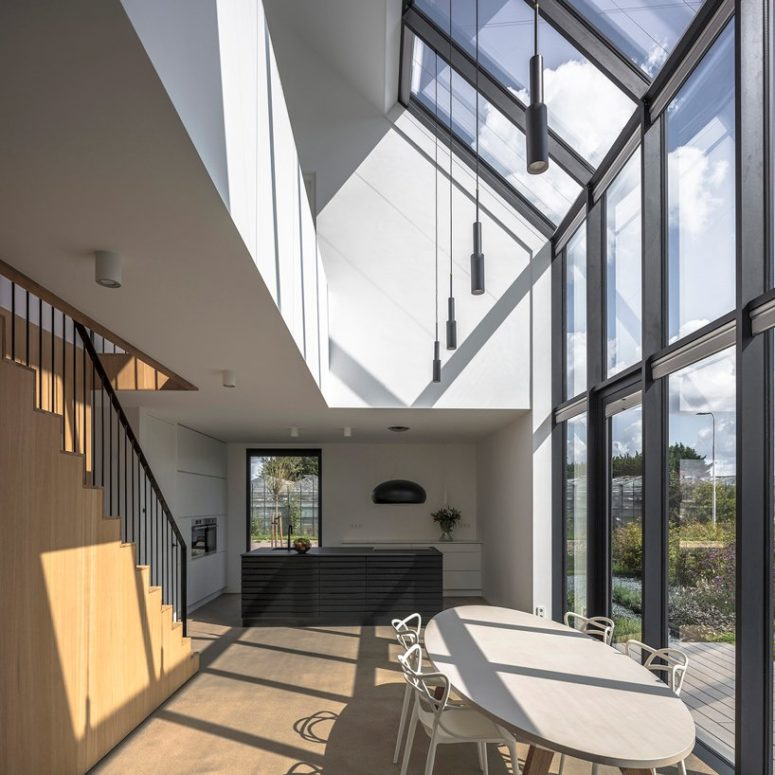 The kitchen and dining spaces are united into one featuring a double height ceiling with a glazed wall and minimal furniture